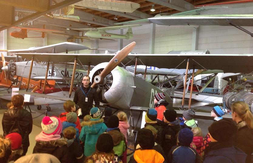 Ryhmä ihailemassa lentokonetta ilmailumuseolla.