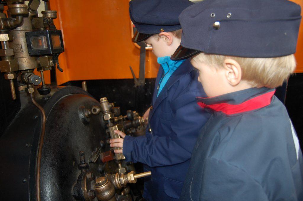 Kaksi lasta veturinkuljettajina Rautatiemuseolla.