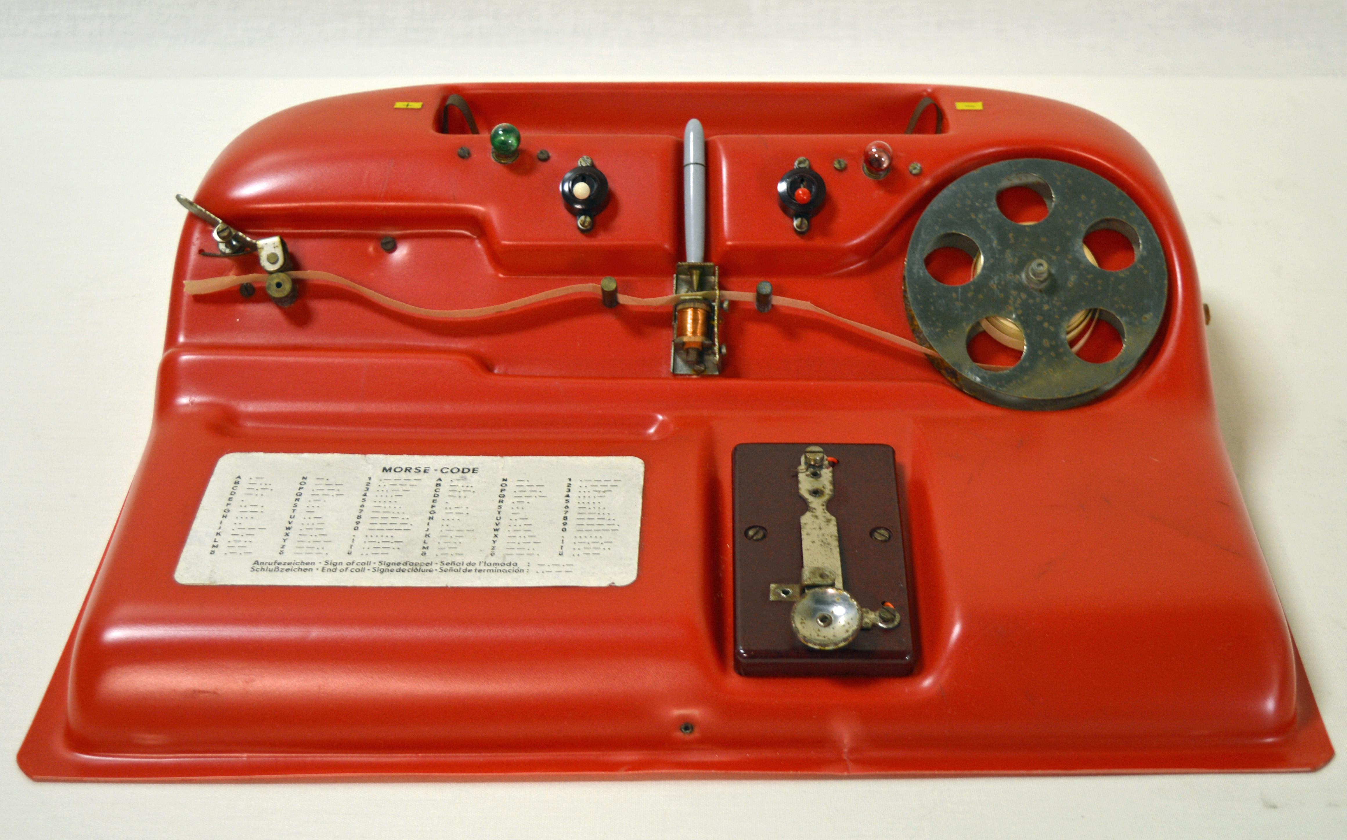 Kirkkaanpunainen sähkötysharjoittelulaite, jossa on erilaisia vipuja ja kiekkoja sähkötystä varten.