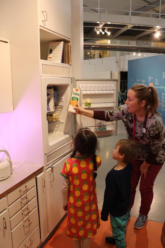 Opas esittelee retrojääkaapin sisältöä lapsille Tekniikan museossa.