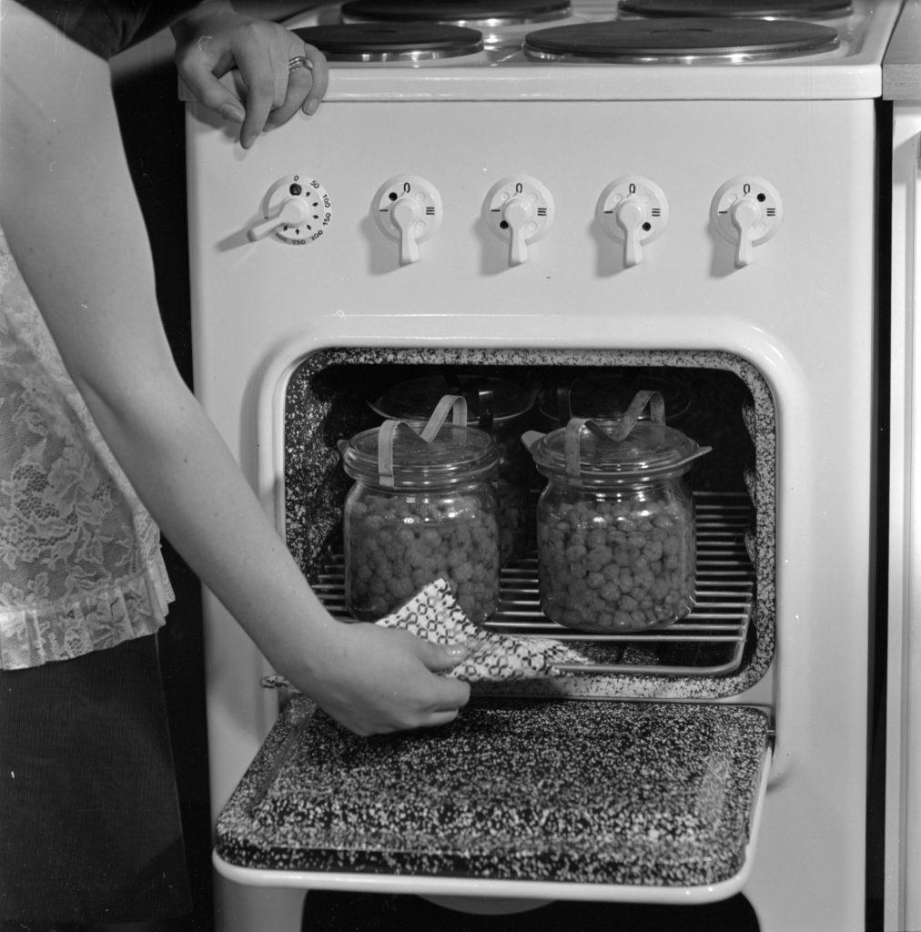 Emäntä ottaa patakintaalla ruokaa pois uunista 1950-luvun mustavalkokuvassa.