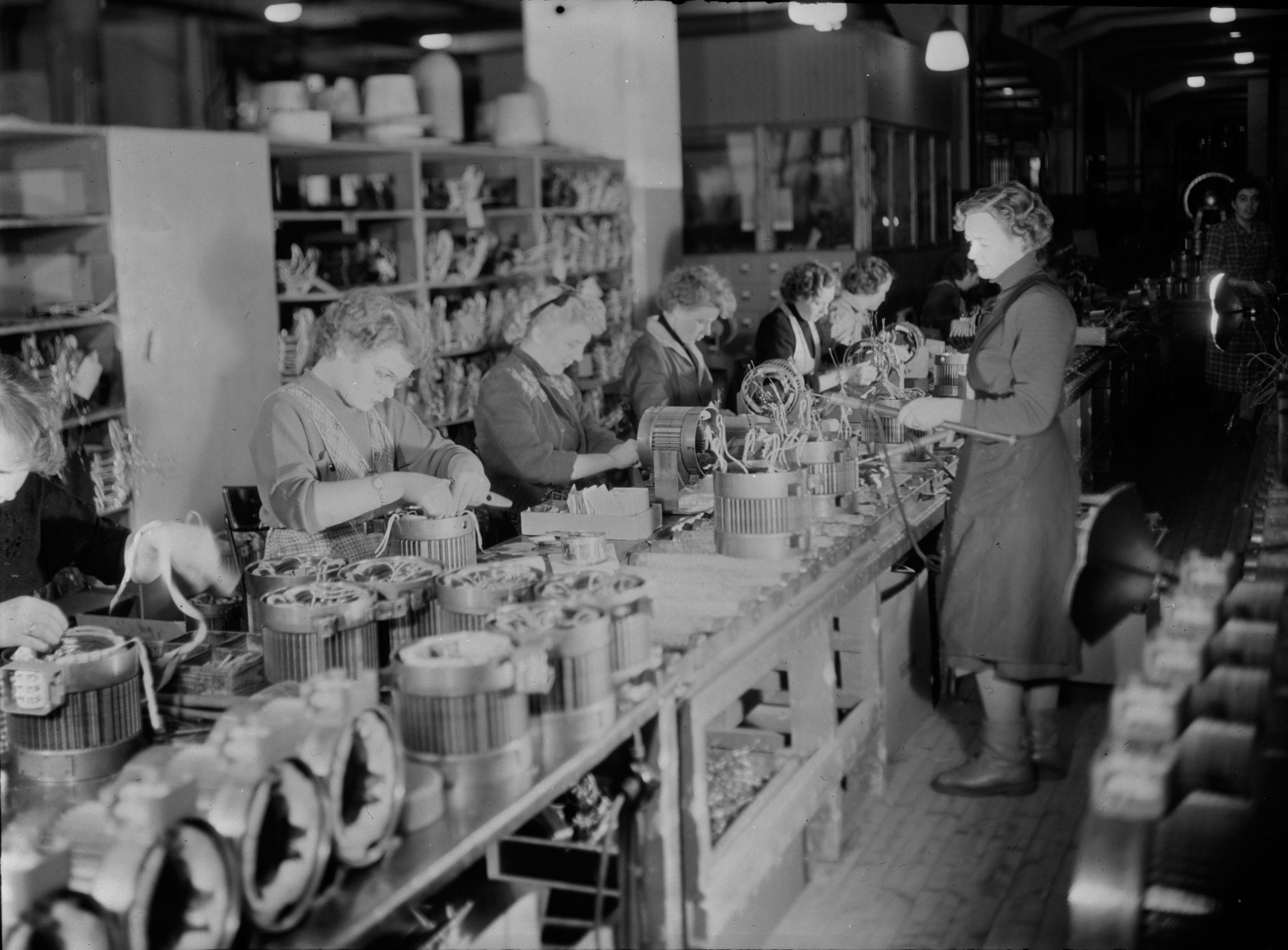 Naisia työskentelemässä Vaasan moottoritehtaan pitkällä liukuhihnalla vuonna 1956. Kuva on osa Tekniikan museon ABB Strömberg -kokoelmaa.