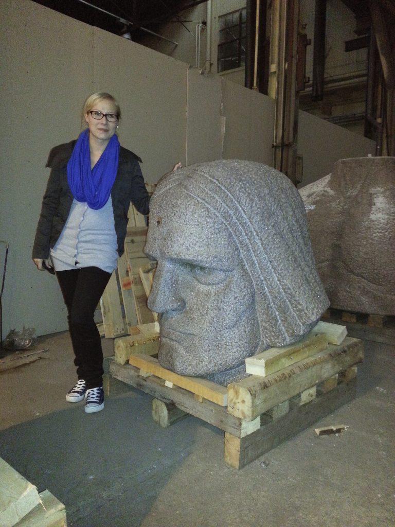 Amanuenssi Ilsi Lantunen poseeraa häntä lantioon ulottuvan kivimiehen pään vieressä hymyillen