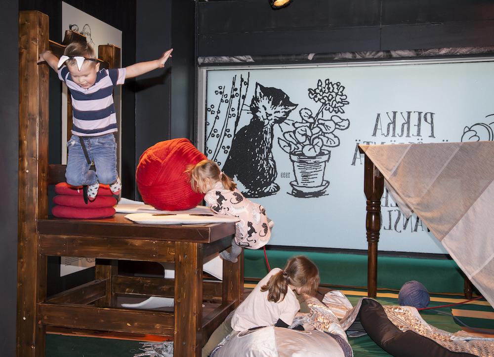 Lapset hyppäävät isolta tuolilta ja makoilevat silakkatyynyllä Pekka Töpöhäntä -näyttelyssä.