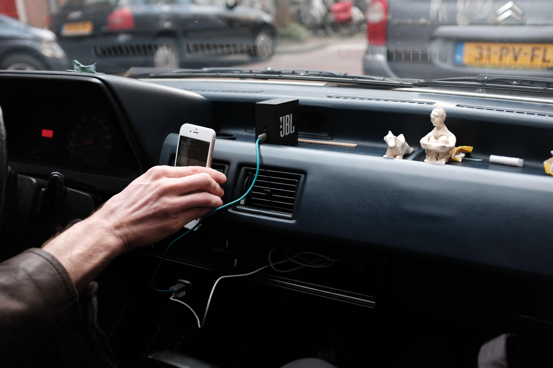 autokuski pitelee kädessään puhelinta, jossa on kiinni pieni matkakaiutin