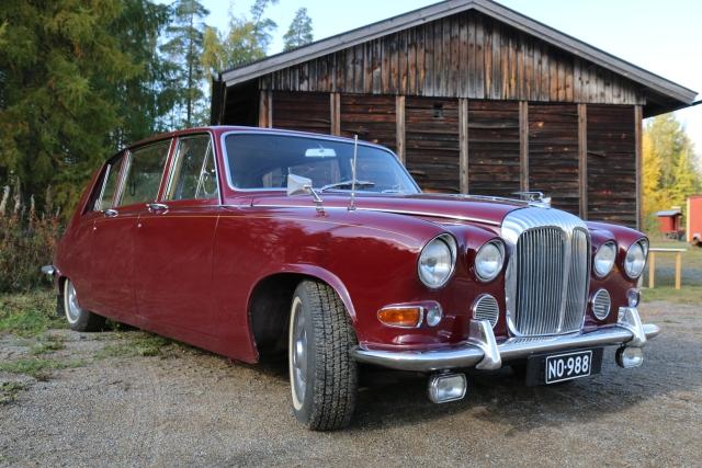Punainen Daimler-limusiini vuodelta 1971 syksyn värjäämässä maisemassa.
