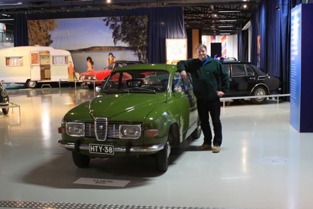 Matti Laurila hymyilee lahjoittamansa Saab96:n vierellä Mobilian Leveillä lahkeilla -näyttelyssä.