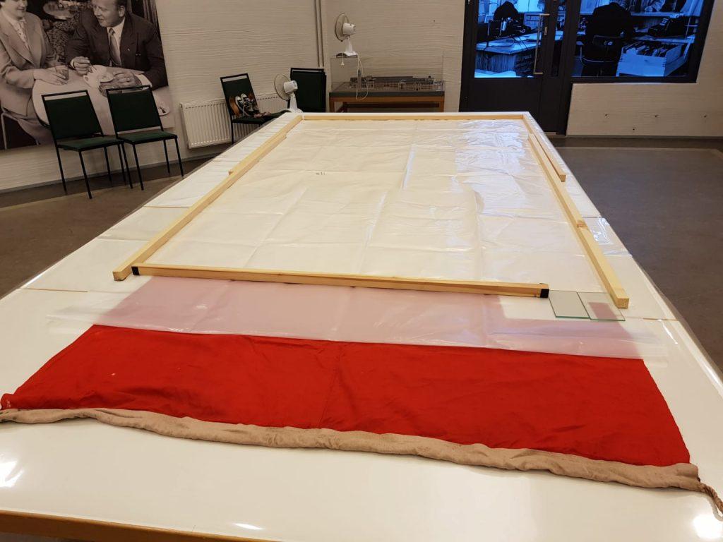 Punainen lippu lepää pöydällä valkoisessa kosteushauteessa.