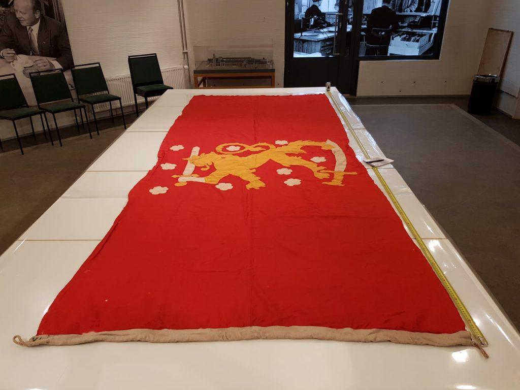 Hehkuvan punainen tekstiili lepää neljällä pöydällä mittojen ottoa varten.
