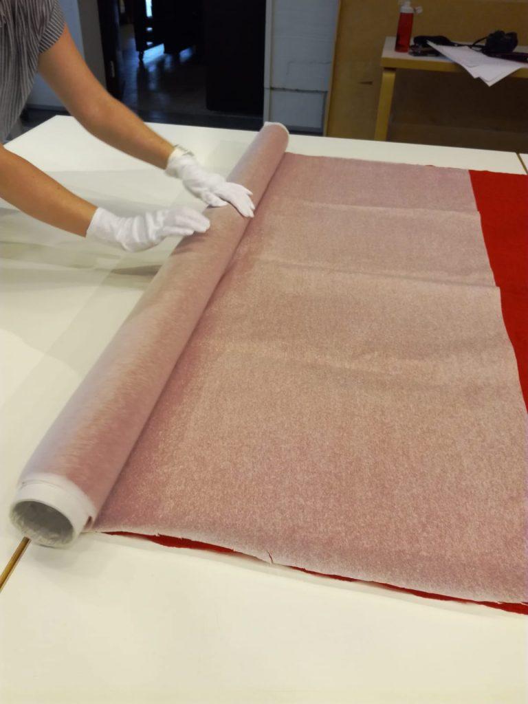 Hansikkailla suojatut kädet käärivät punaista lippua rullalle huolellisesti.