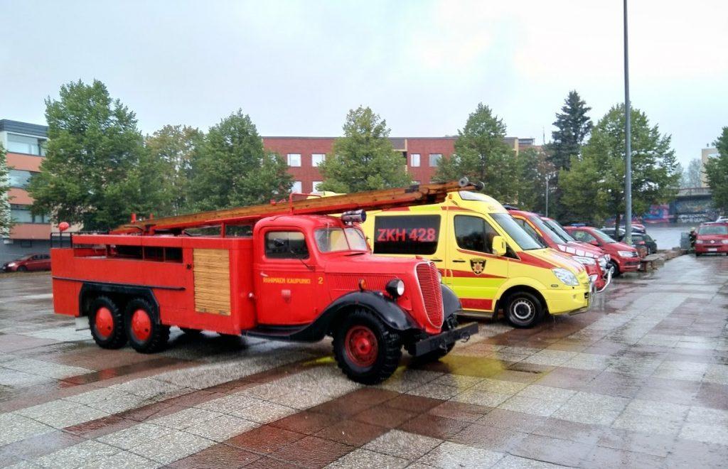 vanha punainen tikaspaloauto parkkipaikalla modernien pelastusautojen vieressä