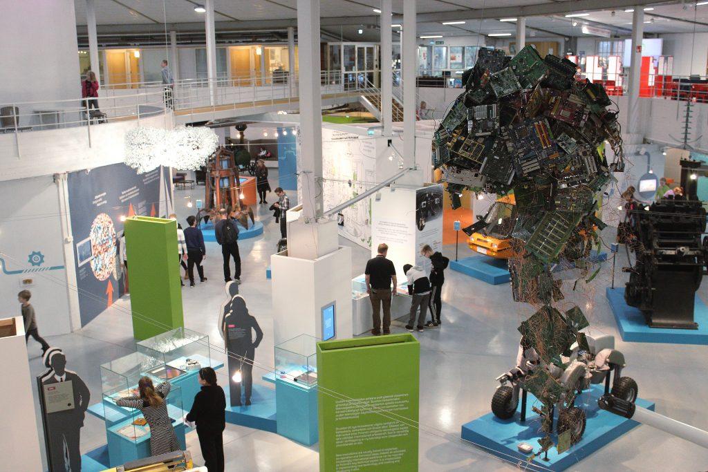 Tekniikan museon näyttelytiloissa vilisee ihmisiä, jotka seisoskelevat esineiden edessä kirkkaassa valaistuksessa.
