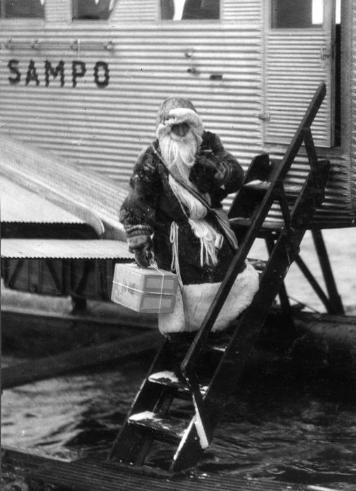 Joulupukki laskeutuu tikkaita alas lentokoneesta mustavalkoisessa kuvassa.
