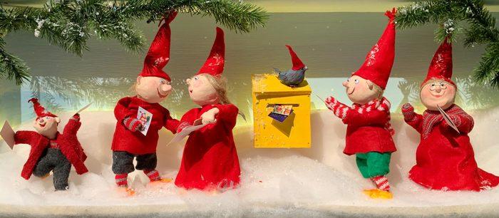 TOntut hyppelevät pumpulista tehdyn lumen päällä. Keskellä töröttää keltainen postilaatikko.