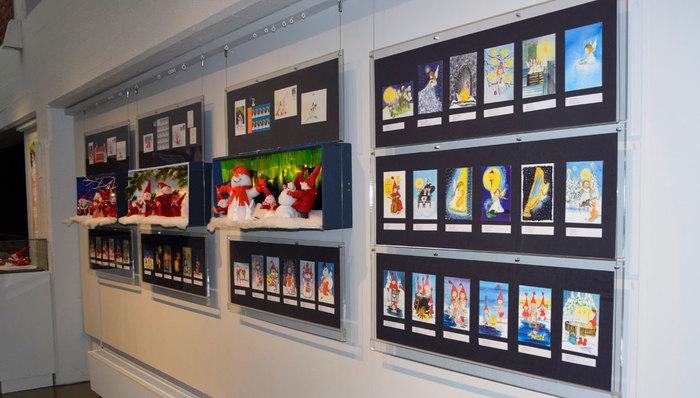 Jouluisia kortteja tummissa kehyksissä museon seinällä.