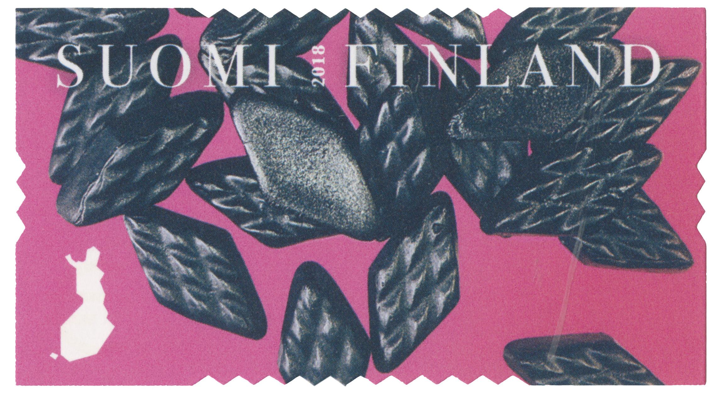 Pinkissä postimerkissä kiiltelee kasa ruudunmuotoisia kiiltäviä salmiakkikarkkeja.