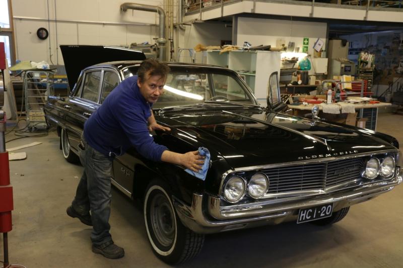 Entistäjä Ismo Koittola viimeistelykiillottaa isoa mustaa Oldsmobilea