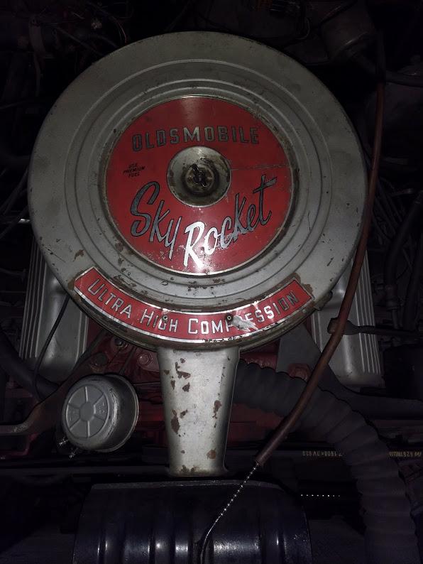 Oldsmobilen moottorissa lukee punaisella pohjalla hopeanharmailla kirjaimilla Sky Rocket