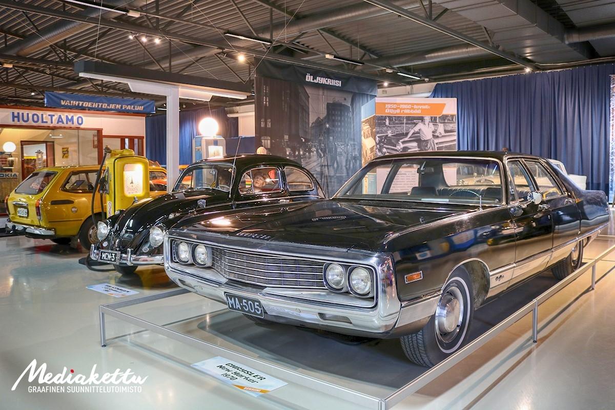Iso musta Chrysler, pieni musta Kupla-Volkkari ja sinapinkeltainen farmari-Toyota huoltamorakennuksen edessä Mobilian näyttelyssä