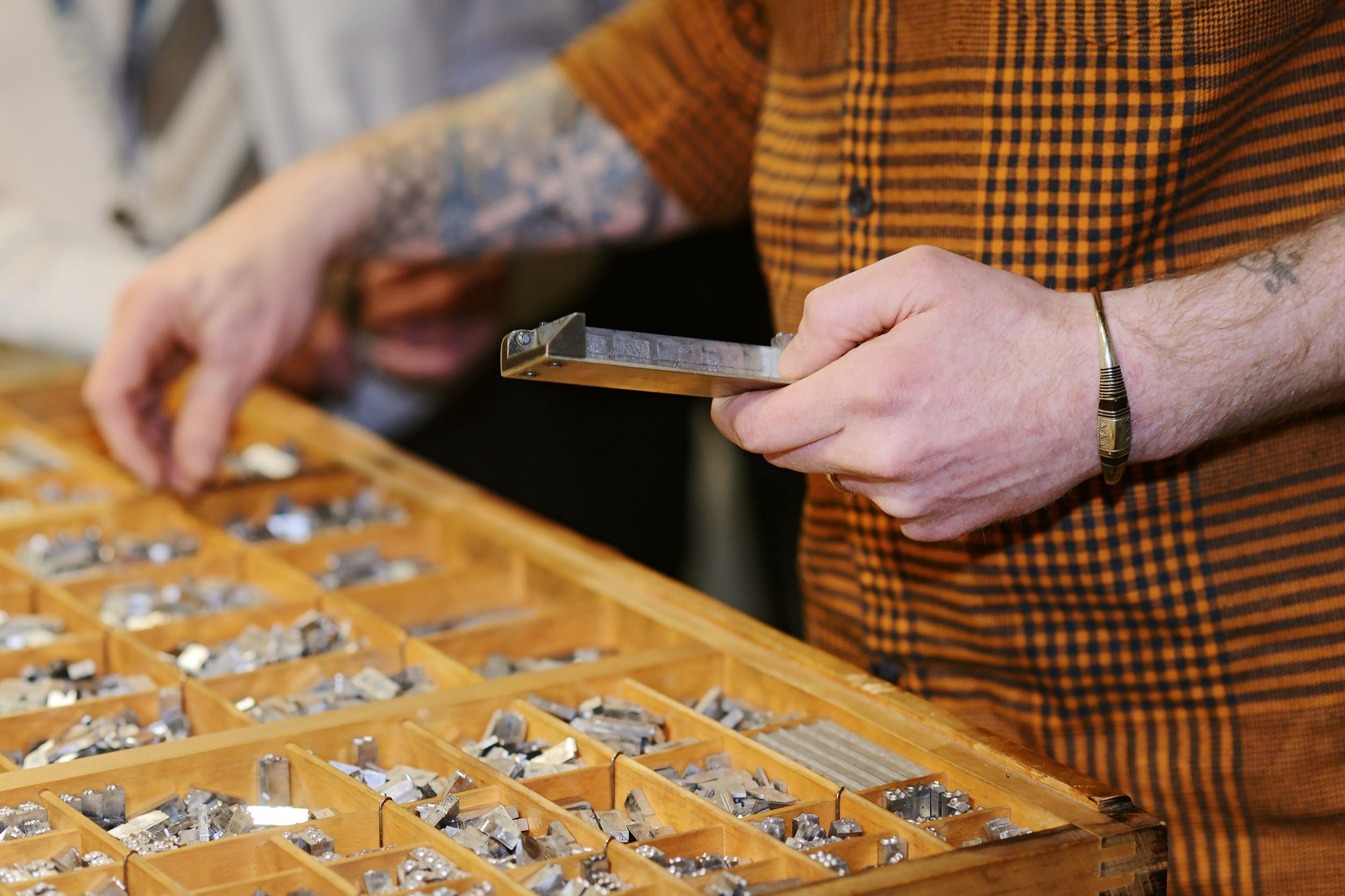Mies poimii kirjaimia puisesta laatikosta metalliseen ladontahakaan. Lähikuva.