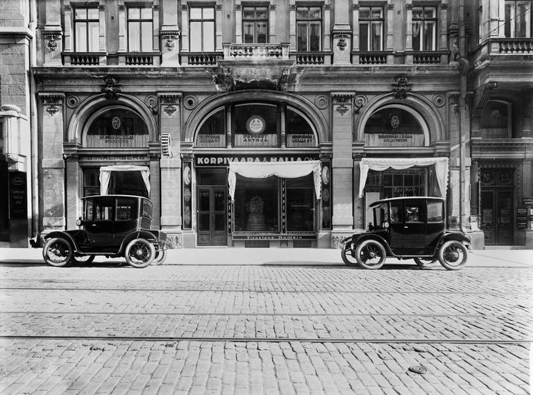 Mustavalkoisessa kuvassa kaksi kantikasta sähköautoa Helsingissä Aleksanterinkatu 15:ssä sijainneen autoliike Korpivaara & Halla Oy:n toimipisteen edessä.