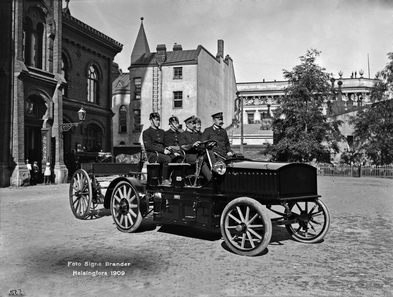 Mustavalkokuvassa sähköpaloauto Helsingin pääpaloaseman pihalla 1909. Taustalla raskas höyryruisku. Autoon mahtui kuljettajan lisäksi neljä miestä. Se oli varustettu hiilihapporuiskulla ja letkurattailla.