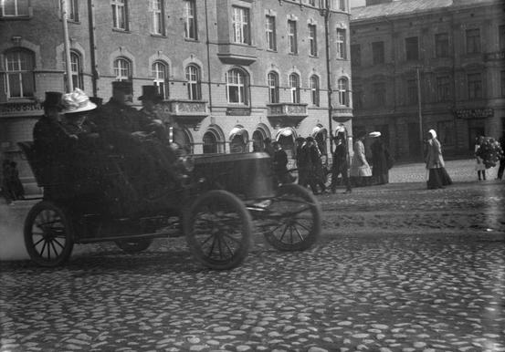 Mustavalkokuvassa höyryauto ajossa Tampereen Keskustorin mukulakivikadulla. Matkustajilla silinterit ja leveä lierihattu.