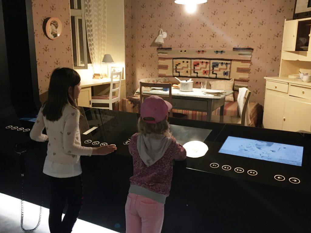 Kaksi kouluikäistä tyttöä katselee museoon rakennettua vanhanajan sisustusta kosketusnäyttöpöydän ääressä Postimuseossa.