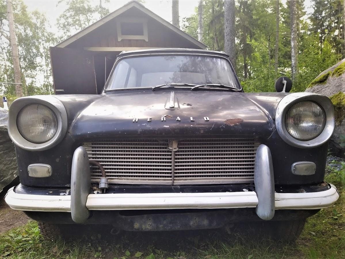 Lähikuva vuoden 1964 Triumph Heraldin keulasta, siilmiinpistävät pyöreät ajovalot ja selkeä puskuri. Auto on melkoisen kulunut pinnoiltaan.