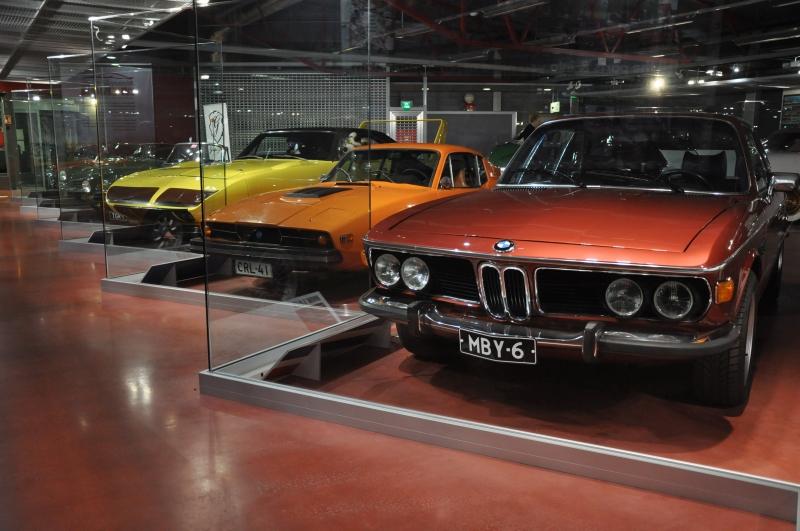 Lasieseinän takana esillä urheilullisen virtaviivaisia autoja, ensimmäisenä viininpunainen BMW.