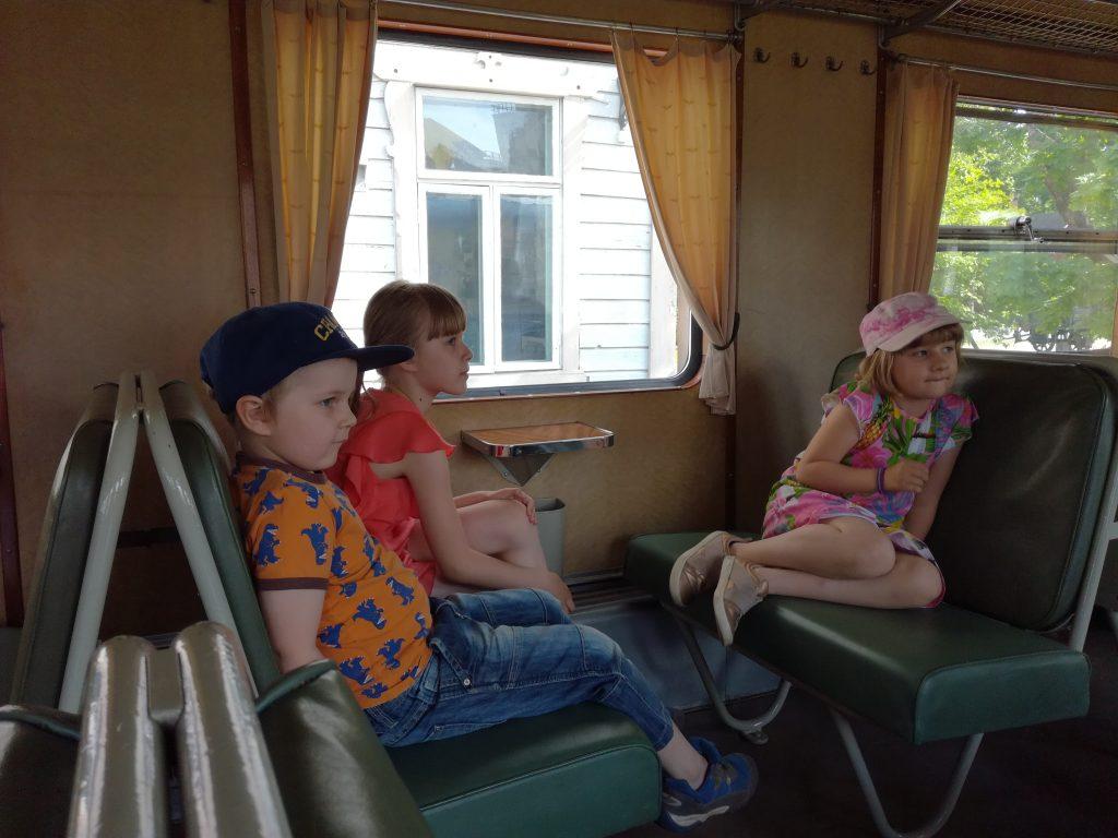 Kolme lasta istuu jännittyneinä Lättähatun istuinloosissa.