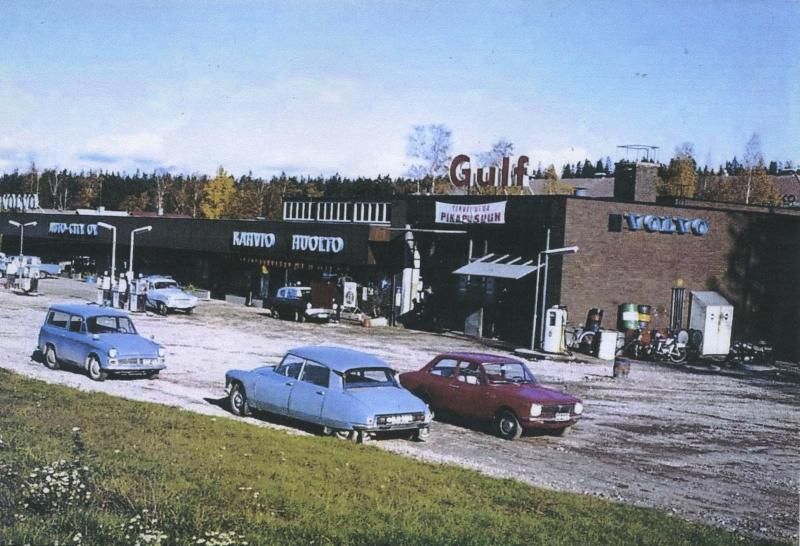 Punatiilisessä liikekiinteistössä sijaitsevan huoltoaseman edessä on parkissa autoja.