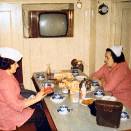 Kaksi naista kahvipöydässä majakkalaivan ahtaassa päällystömessissä. Seinällä pöydän päädyssä on televisio.