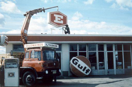 Nosturiauto nostaa E-osuusliikkeen kylttiä huoltoaseman katolle, jossa mies on asentamassa sitä. Gulfin kyltti on maassa.