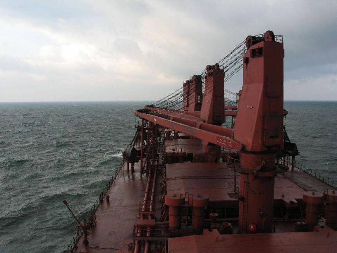 Laivan komentosillalta kuvattu merinäkymä. Kuvassa näkyy tiilenpunaista laivan kantta ja laivan nostureita keulan suuntaan kuvattuna.