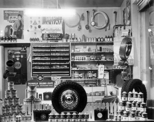 Mustavalkoisessa kuvassa huoltoaseman varaosamyymälässä hyllyt ovat täynnä erilaisia tavaroita.