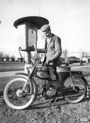 Siististi pukeutunut mies tankkaa mopoa kolikkoautomaatilla toimivasta bensanjakelupylväästä mustavalkokuvassa.