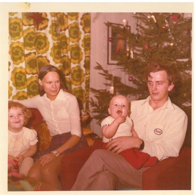 Haalistuneessa värikuvassa 70-luvulta nuoripari pikkulapsensa kanssa joulukuusen edessä.