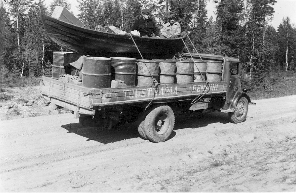 Mustavalkokuvassa kuorma-auton lavalla kuljetetaan bensatynnyreitä, ja niiden päälle on sidottu soutuvene, jossa on kaksi miestä.