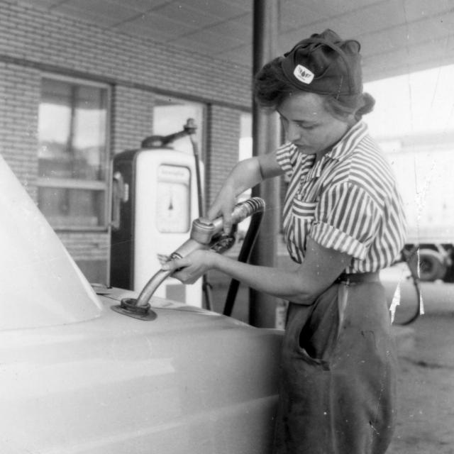 Mustavalkokuvassa Unionin uniformuun pukeutunut nuori tankkaa henkilöautoa.