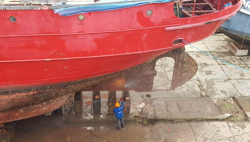 Kuva yläviistosta telakka-altaan pohjalle, jossa mies suihkuttaa vettä majakkalaiva Kemin pohjaan. Aluksen pohja ruosteen värinen, kylki punainen.