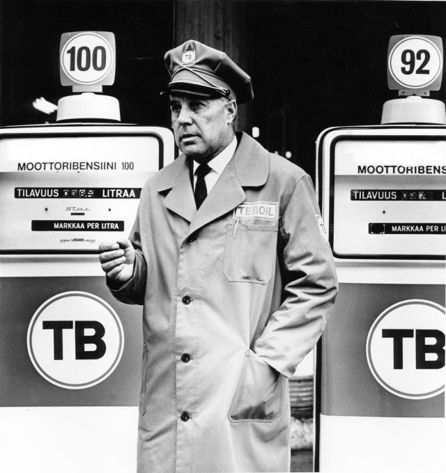 Mustavalkokuvassa vanhempi herrasmies seisoo virkalakki päässään bensamittareiden välissä.