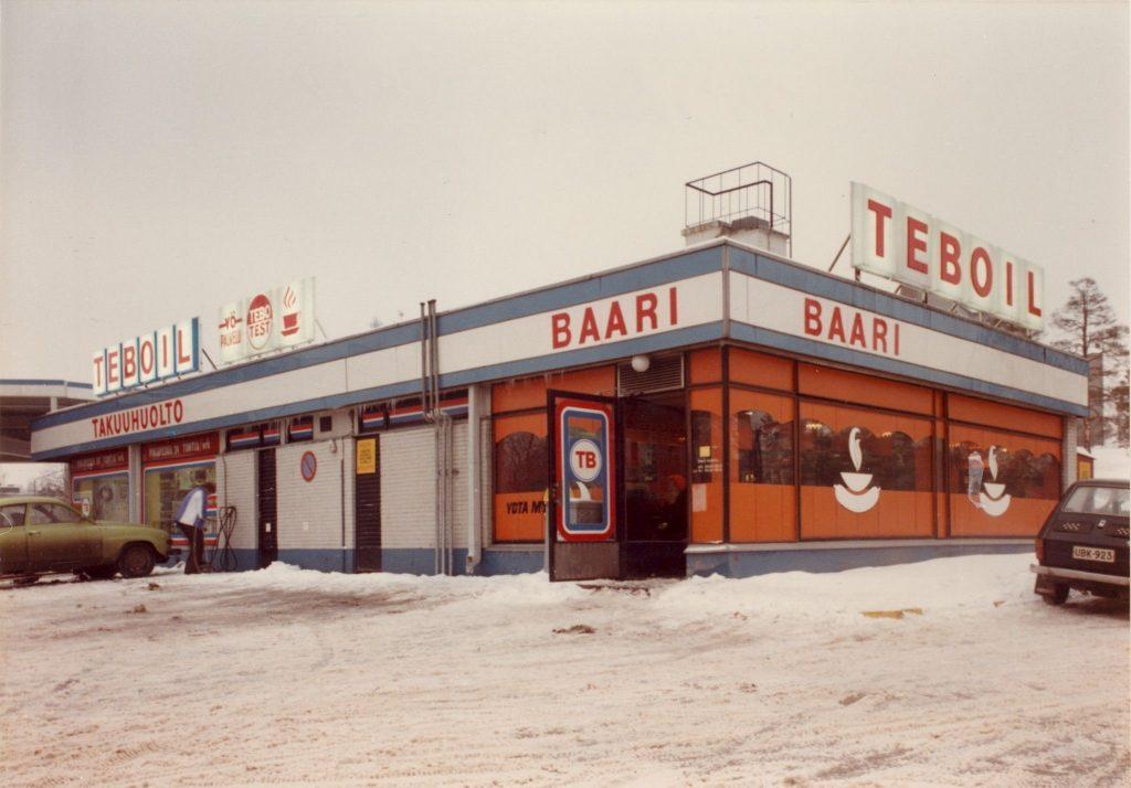 70-luvun kuva Teboilin huoltoasemarakennuksesta, jossa merkittävä osa oli baari ja sen oranssiruskeilla mainoksilla teipatut ikkunat.