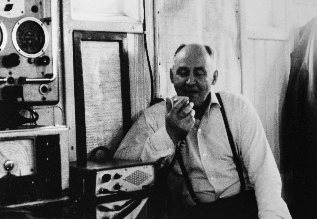 Mustavalkoinen kuva, jossa mies istuu ja puhuu radioon.