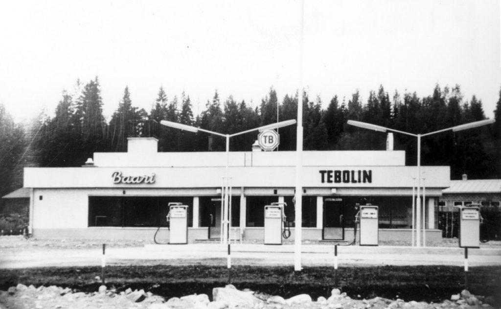 Mustavalkokuvassa vaalea 60-luvun huoltoasemarakennus.