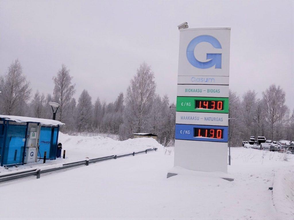 Gasumin hintatoteemi ja biokaasun tankkauspiste lumisessa talvimaisemassa.