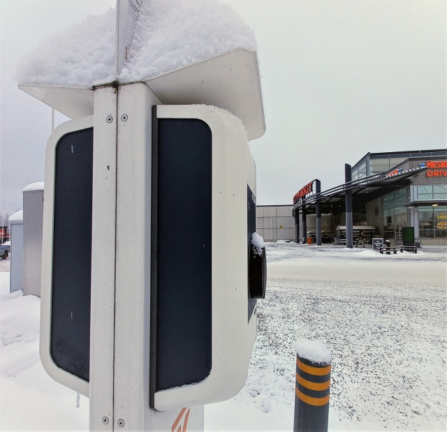 Lumisella parkkipaikalla sähköauton lataustolppa.