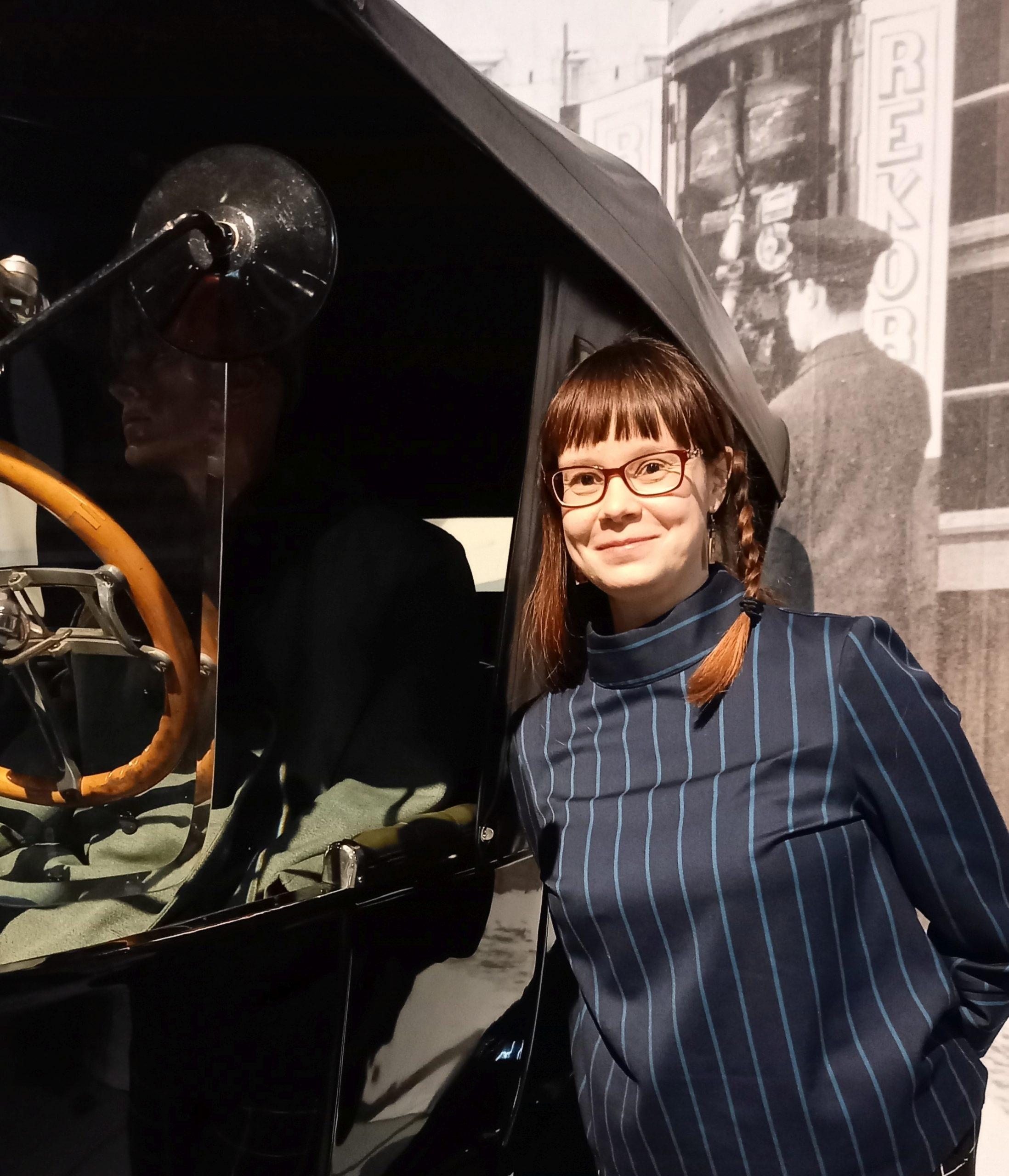 Kirjailija Terhi Rannela siniraitaisessa paidassa vanha T-fordin vieressä.