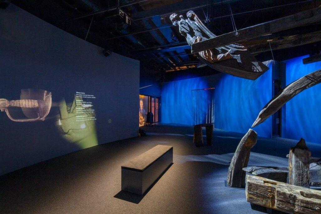 Hämärä näyttelytila, jossa roikkuu laivan keulakuva ja hylyn osia. Seinälle heijastettu miekan kahvan ha hylyn 3D-mallinnos.