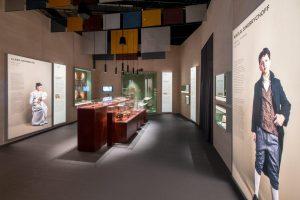 Vaalea näyttelytila, jossa kaksi isokokoista henkilökuvaa. Etualalla Nikolai Sinebrychoffia esittävä, nykyaikainen valokuva. Kauempana vitriineitä.